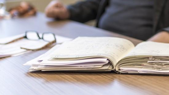 Auf dem Tisch liegt ein Kalender voller Notizen