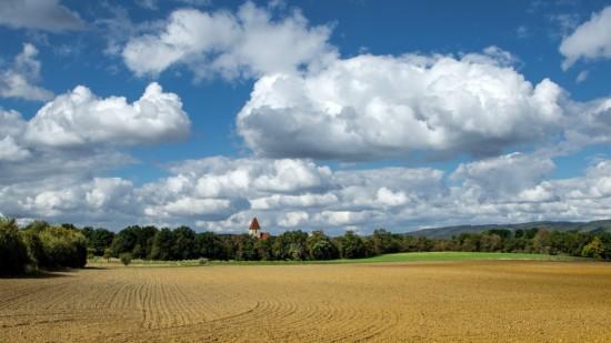 Das Symbolbild zeigt ein Dorf hinter einem Feld