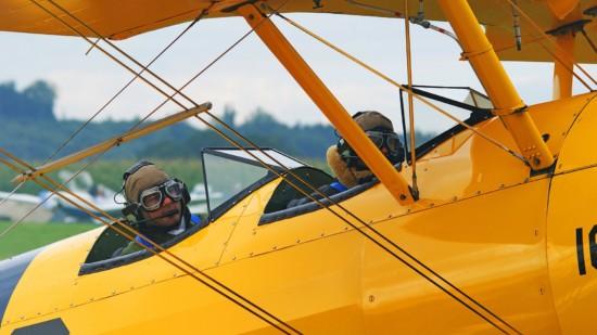Symbolbild: Zwei Flieger sitzen in einem Oldtimerflugzeug