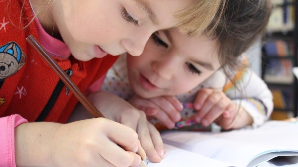 Symbolbild: Zwei Schulkinder schauen gemeinsam in ein Schulheft